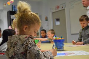 child drawing with a marker with other students
