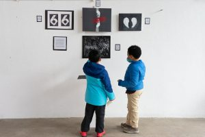 two boys looking at art together in blue